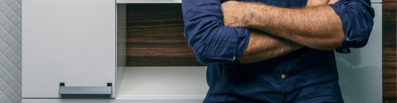 Möbelgriffe – Verschrenkte Arme neben Schrank mit Möbelgriff