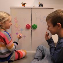 Bunte Möbelknöpfe für das Kinderzimmer und spielende Kinder
